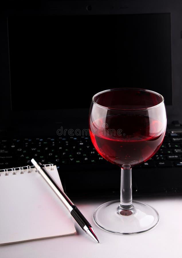 Verre à vin, ordinateur portable et carnet photographie stock libre de droits