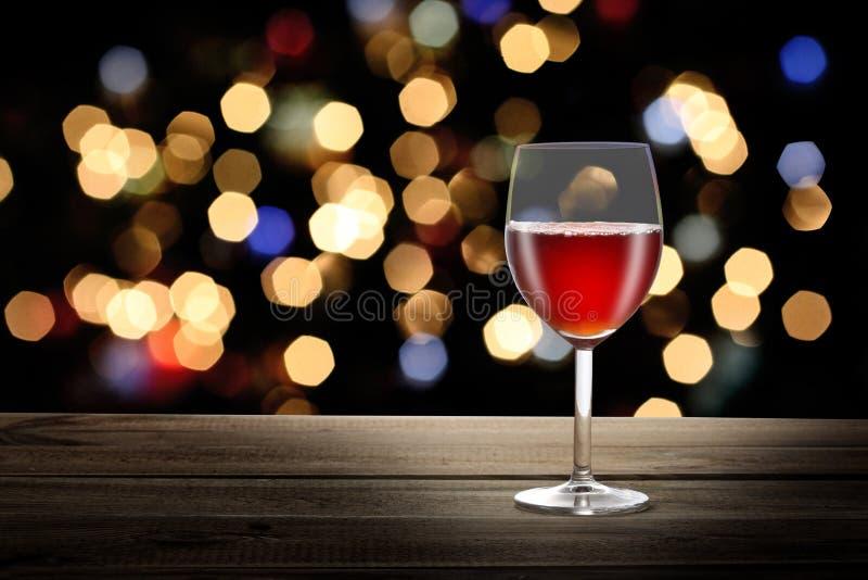 Verre à vin rouge sur une table en bois avec des lumières de bokeh de partie de nuit sur l'espace de fond et de copie pour votre  photo libre de droits
