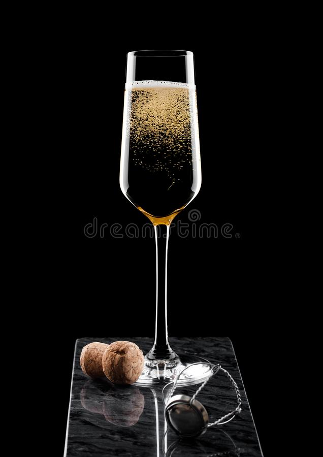 Verre élégant de champagne jaune avec la cage de liège et de fil sur le conseil de marbre noir sur le fond noir photos libres de droits