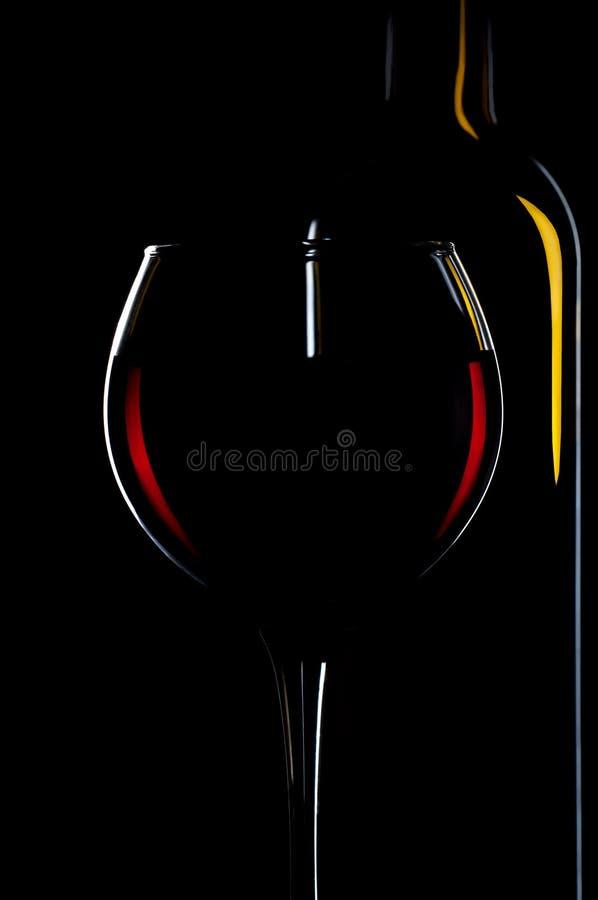 Verre élégant de vin rouge et bouteilles de vin à l'arrière-plan noir photographie stock libre de droits