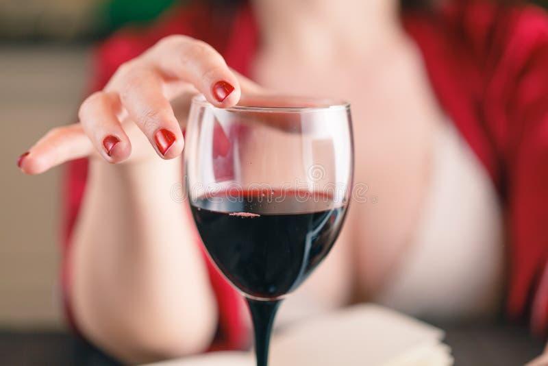 Verre émouvant de femme de vin rouge et d'à l'aide de son ordinateur portable photographie stock