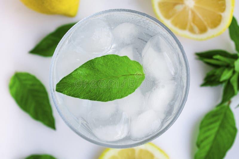 Verre avec de l'eau froide, le citron et la menthe Eau froide sur un fond blanc photos stock