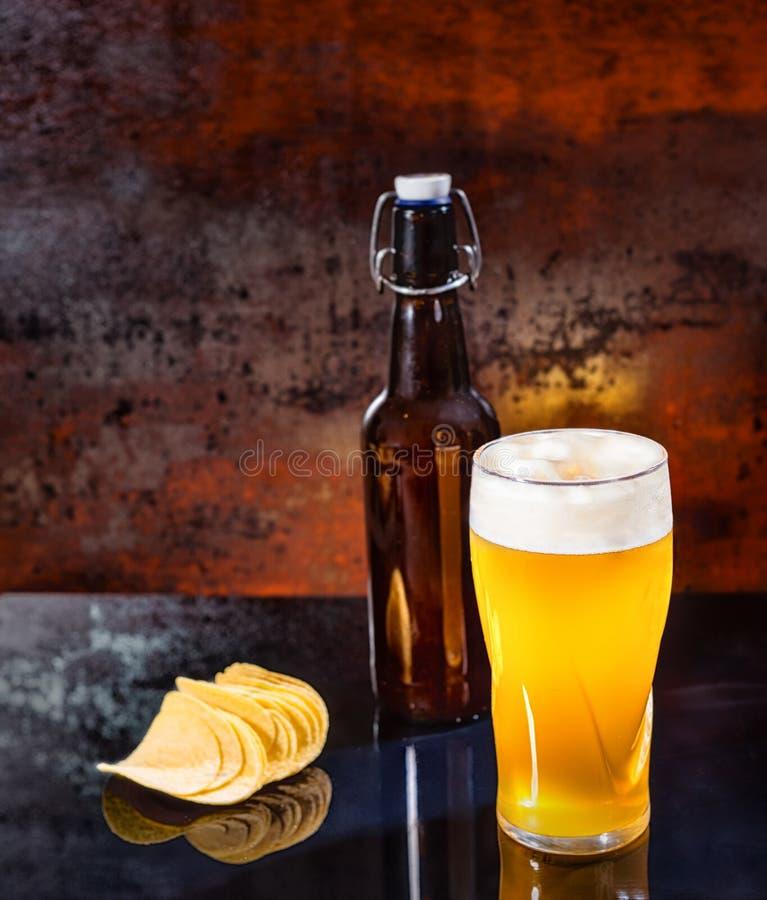 Verre avec de la bière blonde non filtrée fraîchement versée, nea de bouteille à bière image libre de droits