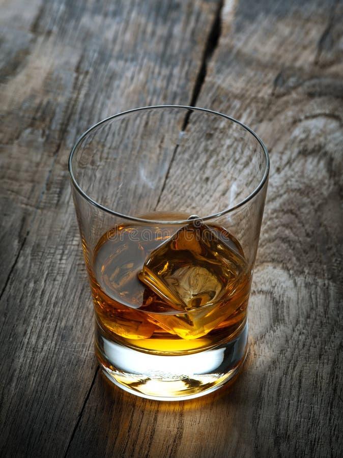 Verre avec de la glace et le whiskey sur le fond en bois image libre de droits