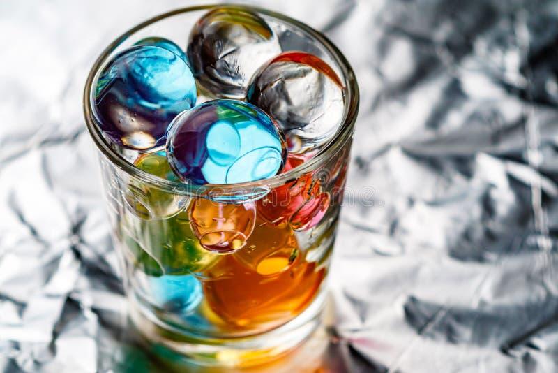 Verre avec des boules d'hydrogel de couleur différente sur la feuille métallique photos libres de droits