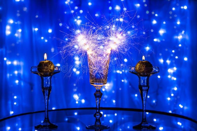 Verre avec des cierges magiques et des bougies sur le fond bleu brouillé image libre de droits