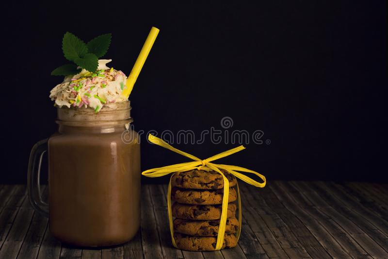 Verre avec du cacao et les biscuits fouettés de crème et de pile image libre de droits