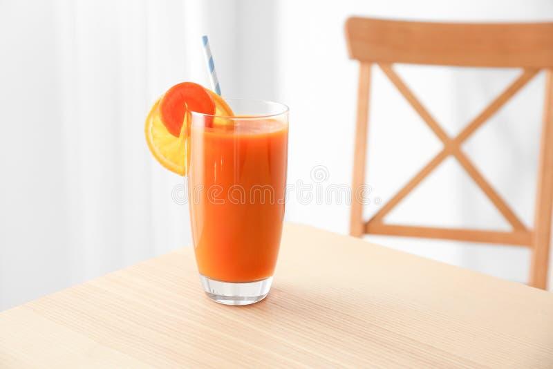 Verre avec du jus frais, la carotte et les tranches oranges images stock