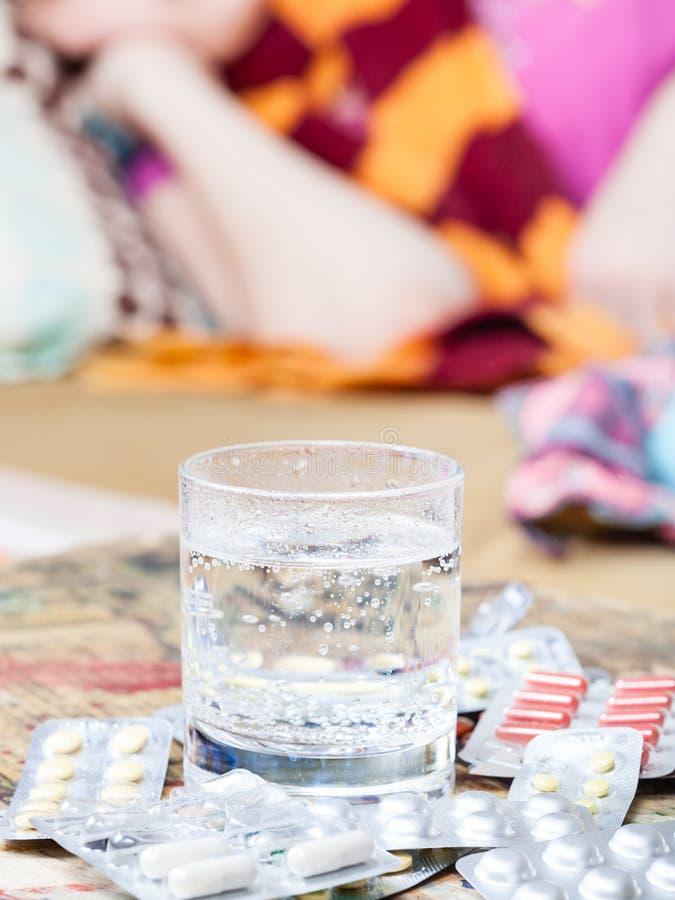 Verre avec du médicament et pilules sur la fin de table  image stock
