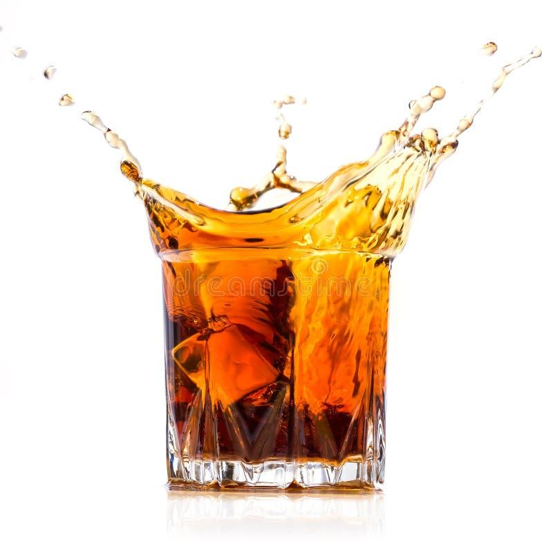 Verre avec l'éclaboussure de whiskey photo stock