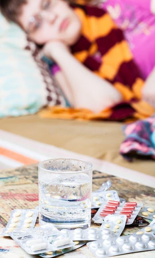 Verre avec l'eau et des médicaments sur la table photographie stock libre de droits