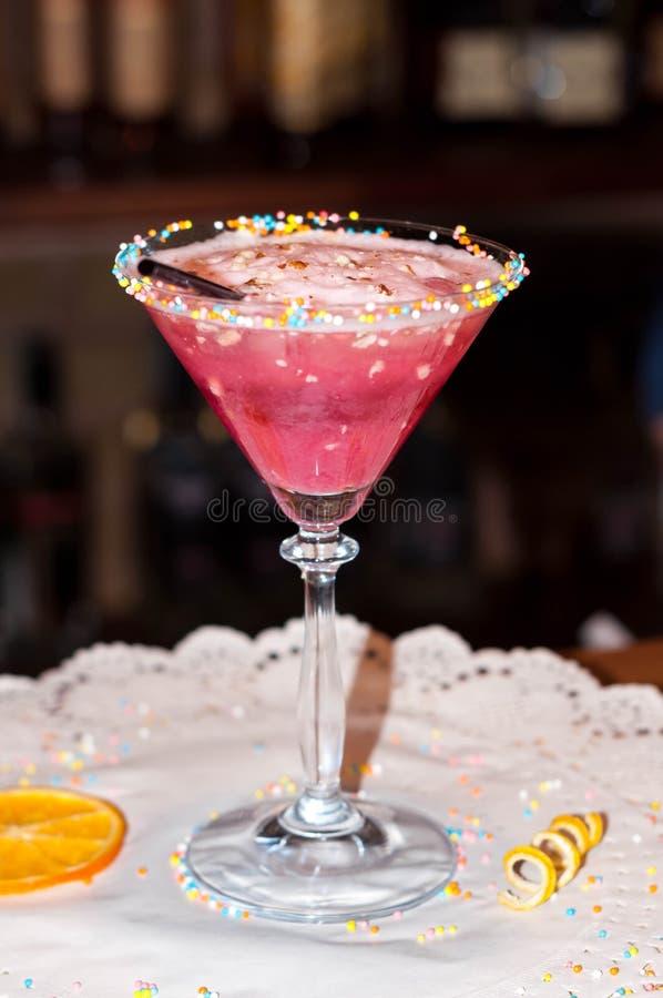 Verre avec la boisson rouge d'alcool et paille sur la serviette de livre blanc avec la tranche orange sèche photographie stock libre de droits
