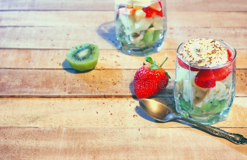 Verre avec la salade de fruits sur la table en bois photographie stock libre de droits