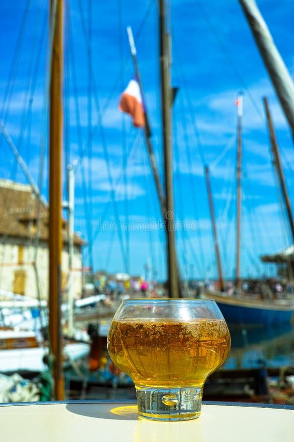 Verre avec le cidre de pomme savoureux dans le vieux village français de pêcheur, non photo stock