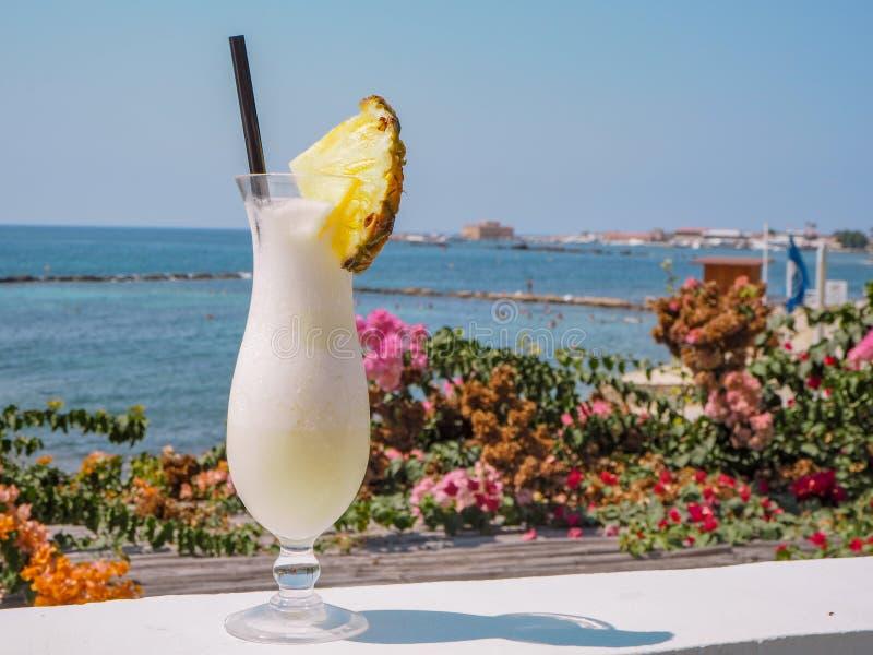 Verre avec le cocktail frais de colada de pina avec dans le dos la baie et le château de Paphos, Chypre photos libres de droits