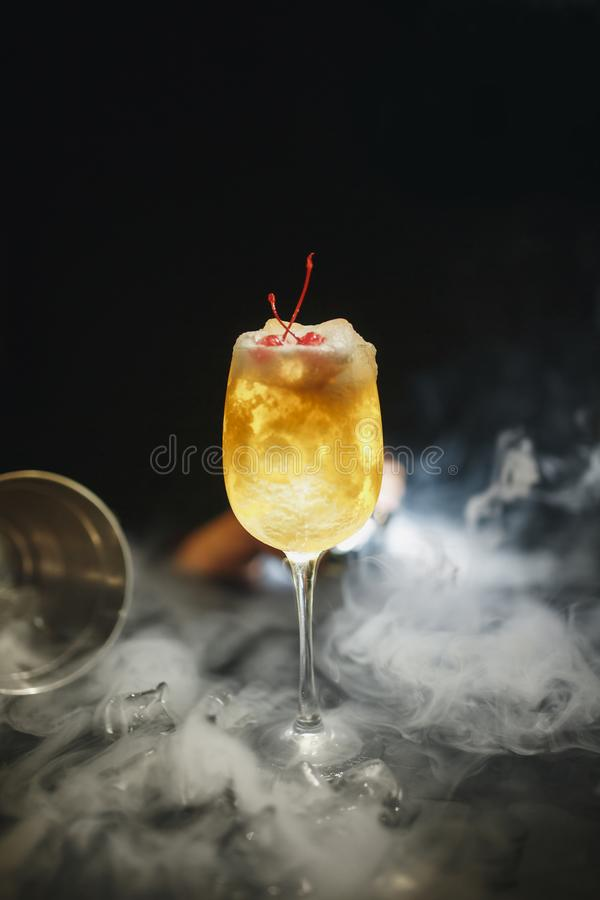 Verre avec le cocktail jaune d'ananas sur la barre sur un fond noir la boisson est décorée de la cerise avec de la fumée image libre de droits