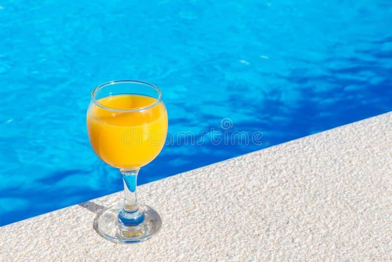 Verre avec le jus d'orange sur le bord de la piscine photo stock