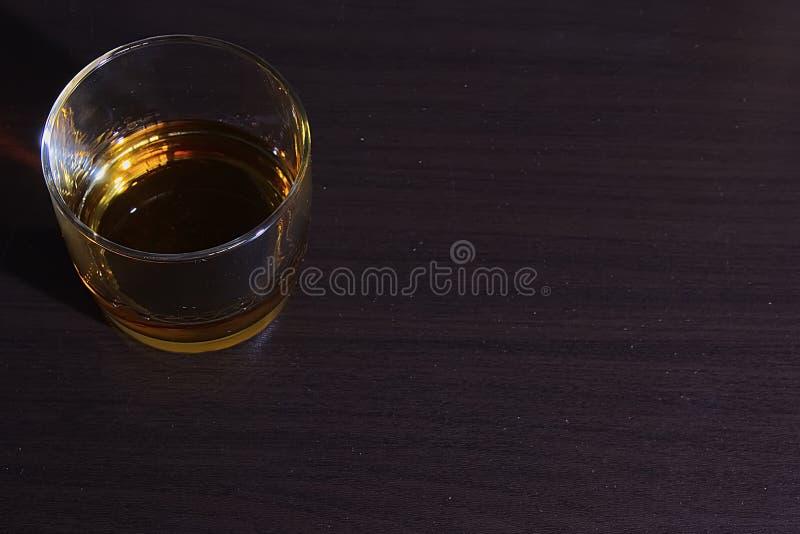 Verre avec le rhum d'isolement sur une table en bois fonc image stock
