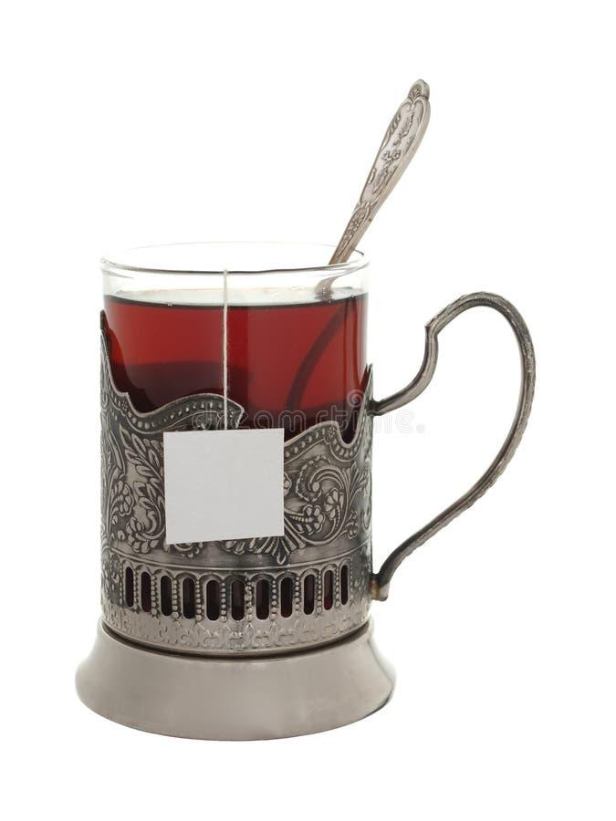 Verre avec le thé et une cuillère à café dans un support de tasse d'isolement sur un petit morceau photo stock