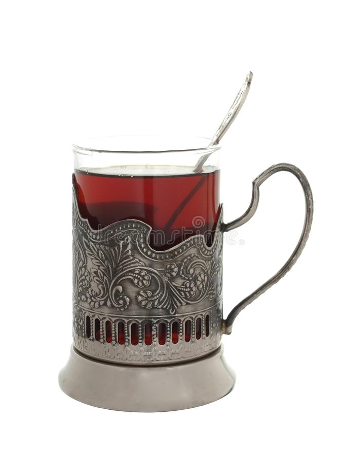 Verre avec le thé et une cuillère à café dans un support de tasse d'isolement sur un petit morceau image libre de droits
