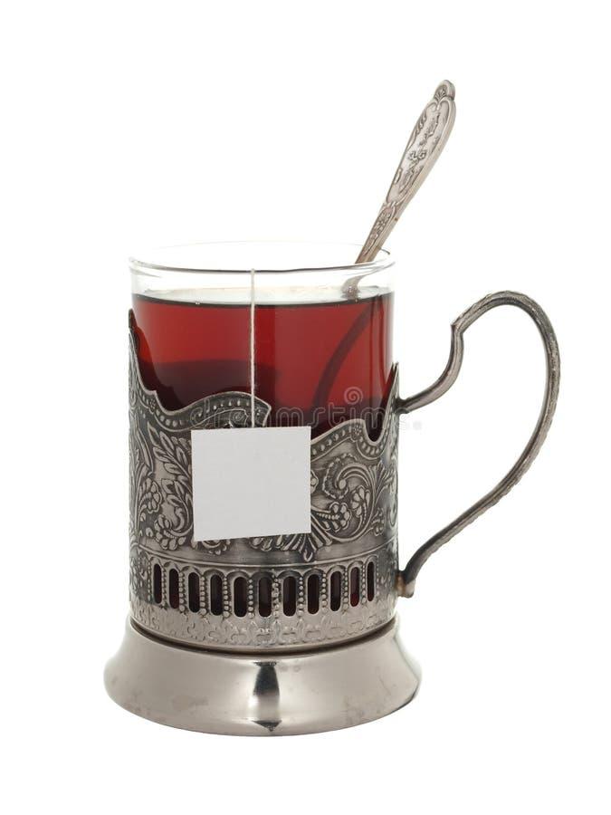 Verre avec le thé et une cuillère à café dans un support de tasse d'isolement sur un petit morceau photo libre de droits
