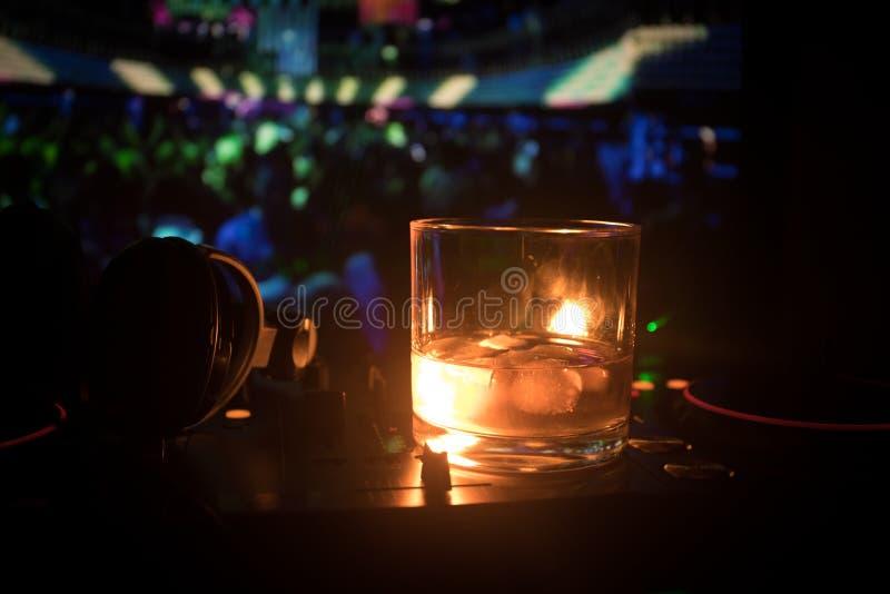 Verre avec le whiskey avec le glaçon à l'intérieur sur le contrôleur du DJ à la boîte de nuit Console du DJ avec la boisson de cl photographie stock libre de droits