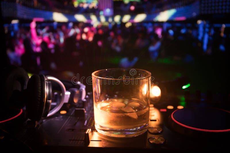 Verre avec le whiskey avec le glaçon à l'intérieur sur le contrôleur du DJ à la boîte de nuit Console du DJ avec la boisson de cl photos stock