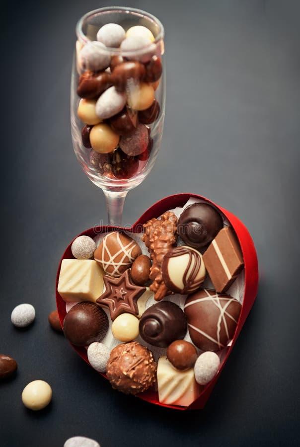 Verre avec les pralines de chocolat et la boîte en forme de coeur avec des pralines images stock