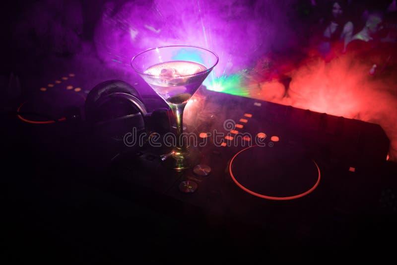 Verre avec martini avec l'olive à l'intérieur sur le contrôleur du DJ dans la boîte de nuit Console du DJ avec la boisson de club images stock
