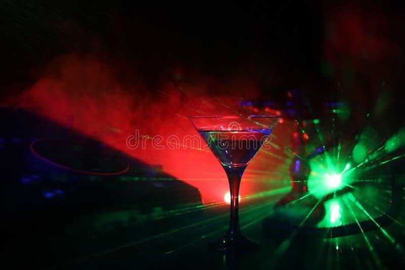 Verre avec martini avec l'olive à l'intérieur sur le contrôleur du DJ dans la boîte de nuit Console du DJ avec la boisson de club photo stock