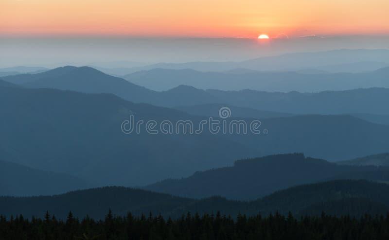 Verre bergketen en dunne laag wolken op de valleien stock foto's