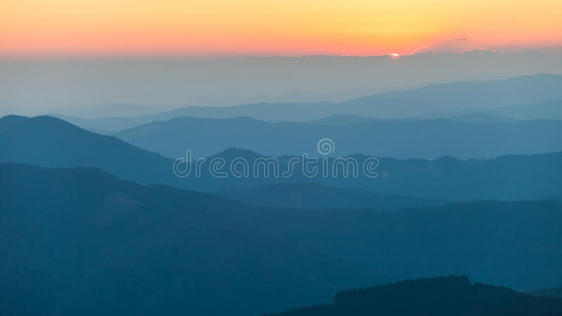 Verre bergketen en dunne laag wolken op de valleien stock afbeelding
