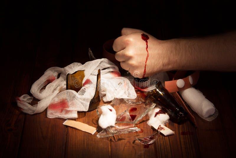 Verre cassé par fragments, bouteilles, et main enroulée d'isolement sur le noir photos stock