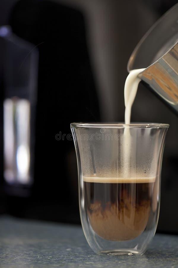Verre chaud de versement de tasse de café de lait image libre de droits