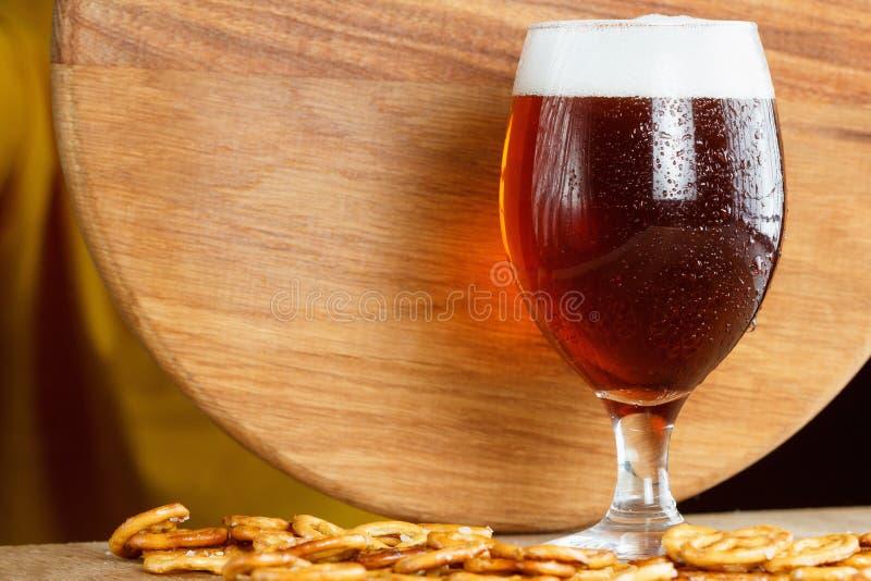 Verre d'alcool mousseux de bière avec le bretzel allemand Casse-croûte et boisson bavarois traditionnels d'Oktoberfest photographie stock libre de droits