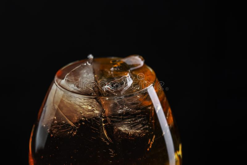 Verre d'eau-de-vie fine en gros plan rempli de whiskey avec de la glace photographie stock