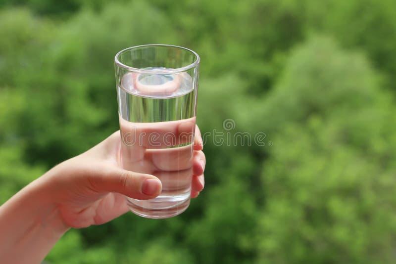 Verre d'eau potable propre dans la main femelle sur le fond brouillé de nature images stock