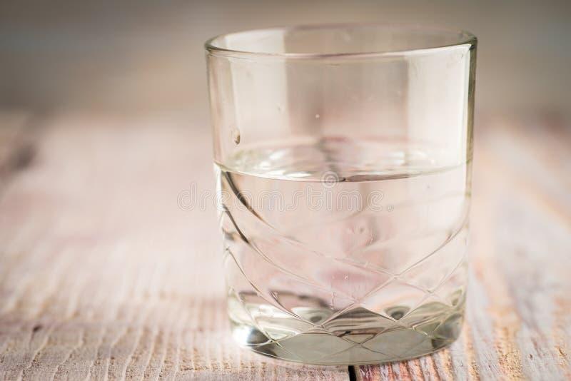 Verre d'eau sur la table en bois avec le fond brouillé photographie stock libre de droits