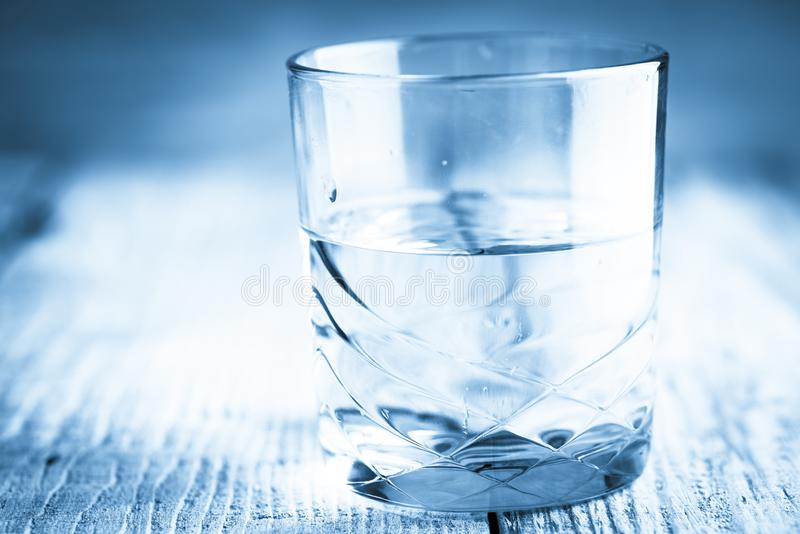 Verre d'eau sur la table en bois avec le fond brouillé images stock