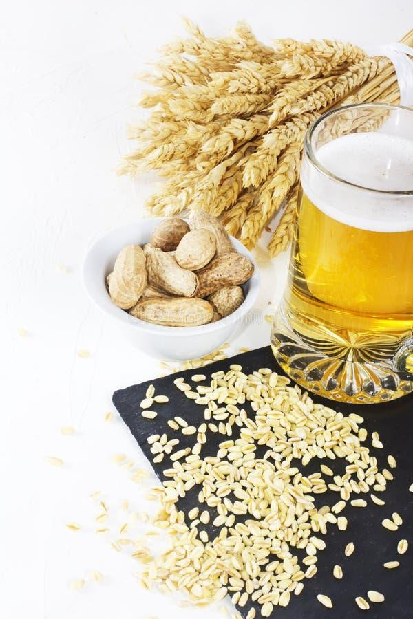 Verre de bière froide avec des frites et des arachides sur le fond blanc image libre de droits