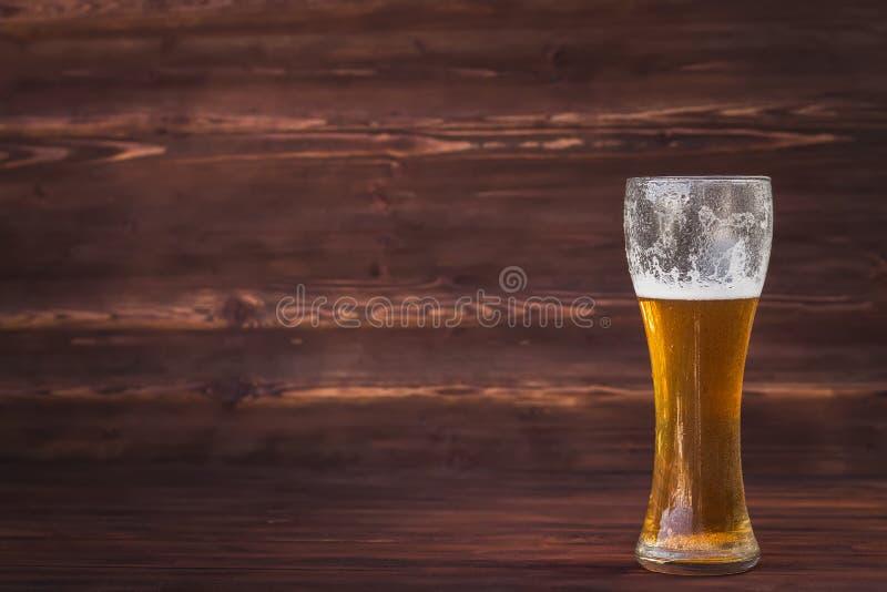 Verre de bière froide sur un fond en bois brun photographie stock