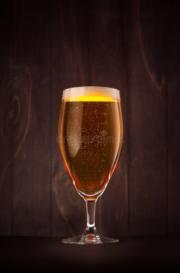 Verre de bière de gobelet avec la bière blonde allemande de scintillement d'or sur le conseil en bois foncé, vertical photos stock