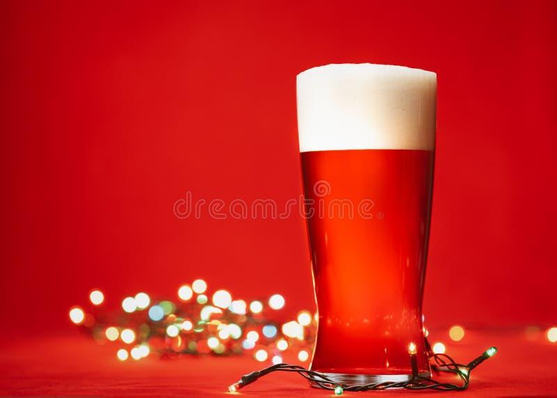 Verre de bière ou de bière anglaise de bière de pilsen avec la grande tête des lumières de mousse et de Noël sur le fond rouge images stock