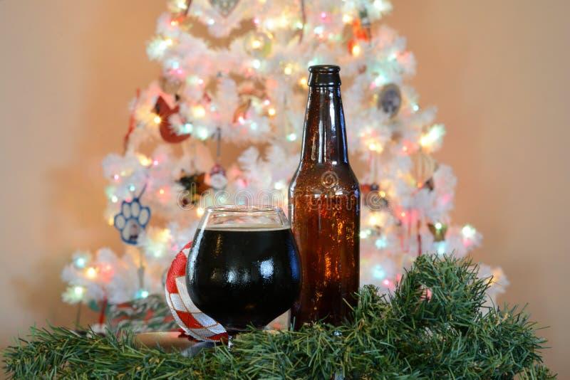Verre de bière posé devant l'arbre de Noël blanc avec les lumières colorées photos libres de droits