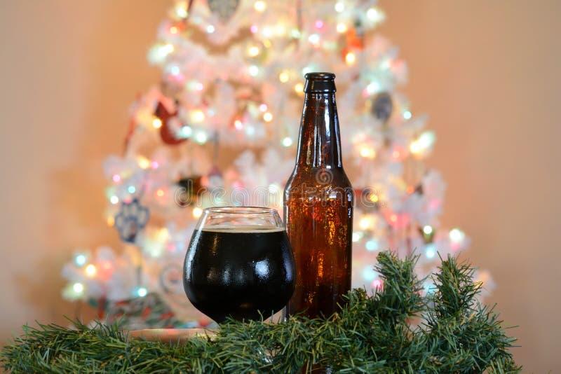 Verre de bière posé devant l'arbre de Noël blanc avec les lumières colorées photos stock
