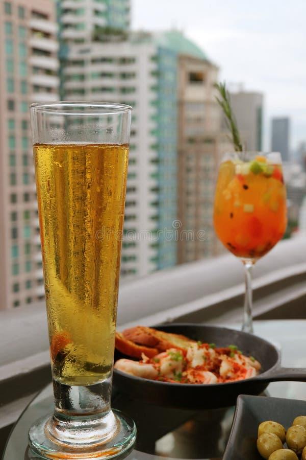 Verre de bière pression effrayante avec le cocktail trouble de sangria de fruits frais et de Tapas à la terrasse de barre de dess photo libre de droits
