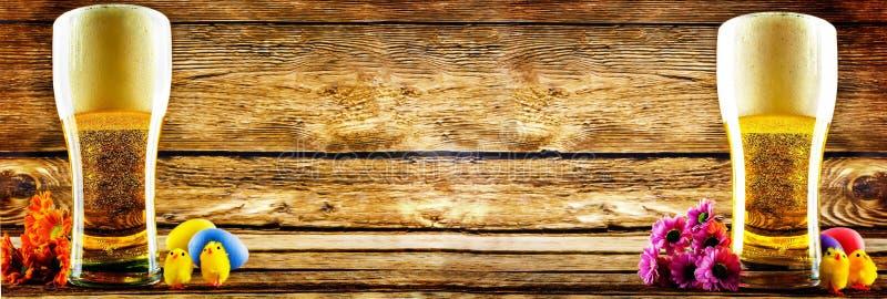 Verre de bi?re de lumi?re froide avec des d?corations de P?ques sur un fond en bois pour les vacances de P?ques photos stock