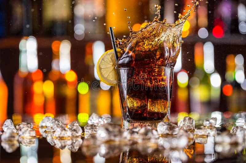Verre de boisson de kola avec l'éclaboussure sur le compteur de barre images libres de droits