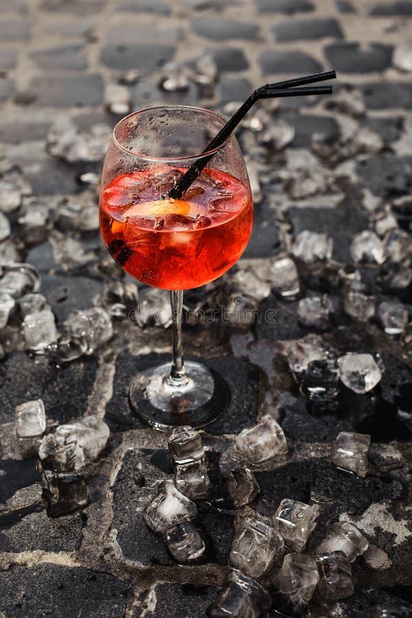 Verre de cocktail avec la boisson et glaçons sur le trottoir photographie stock