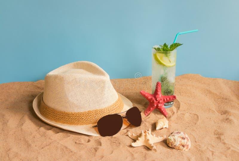 Verre de cocktail, de chapeau, de lunettes de soleil, d'étoiles de mer et de coquillages de mojito sur la plage de sable sur le c photo stock